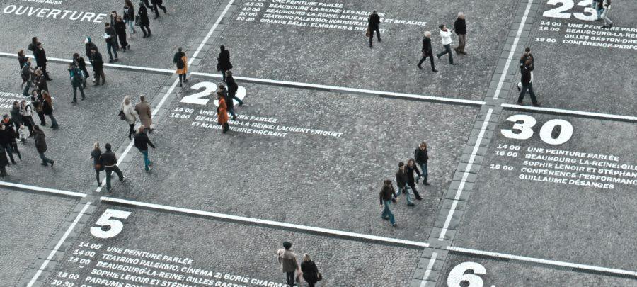 Menschen stehen auf einem großen Platz, der mit Zahlen und Namen beschrieben ist