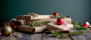 Weihnachtlich verpackte Geschenke liegen vor einem neutralen blauen Hintergrund